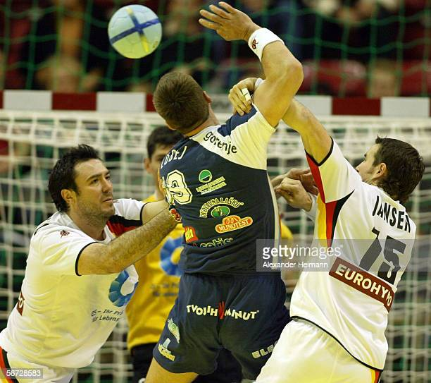 Andrej Klimovets and Torsten Jansen of Germany compete with Uros Zorman of Slovenia during the Handball Euro06 main round match between Slovenia and...