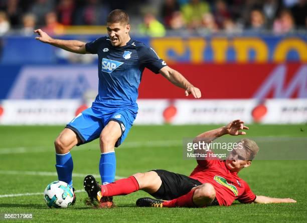 Andrej Kramaric of 1899 Hoffenheim is challenged by Philipp Lienhart of SC Freiburg during the Bundesliga match between SportClub Freiburg and TSG...