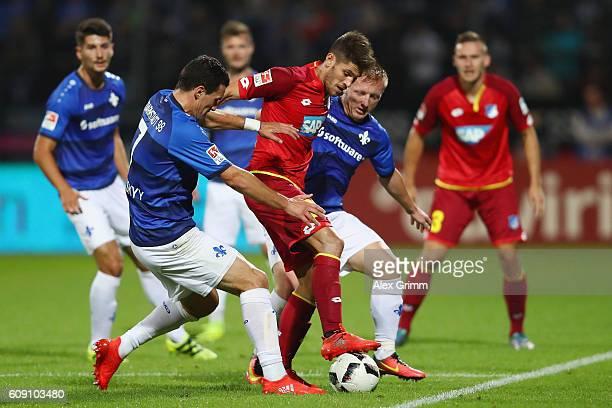 Andrej Kramaric of Hoffenheim is challenged by Artem Fedetskiy /front and Laszlo Kleinheisler of Darmstadt during the Bundesliga match between SV...