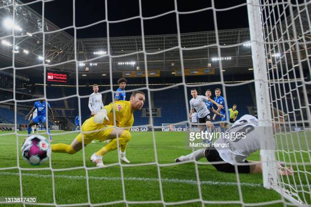 Andrej Kramaric of Hoffenheim scores his team's first goal past goalkeeper Tobias Sippel and Matthias Ginter of Borussia Moenchengladbach during the...