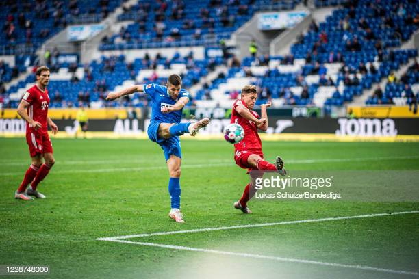 Andrej Kramaric of Hoffenheim scores his teams third goal against Joshua Kimmich of Munich during the Bundesliga match between TSG Hoffenheim and FC...