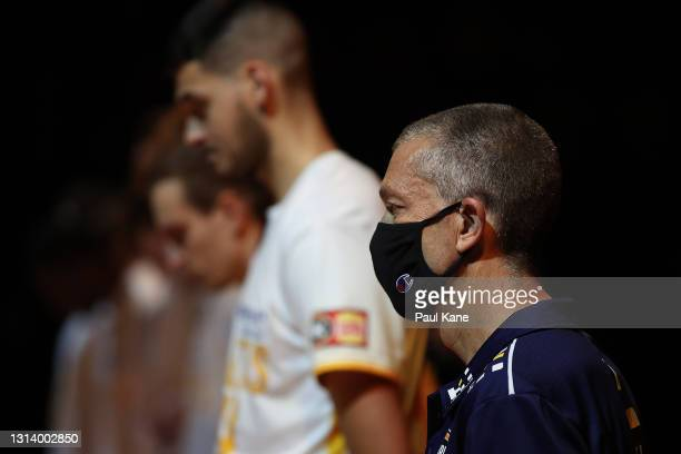 Andrej Lemanis, head coach of the Bullets looks on with his team as the Last Post is played to commemorate the ANZAC's during the round 15 NBL match...