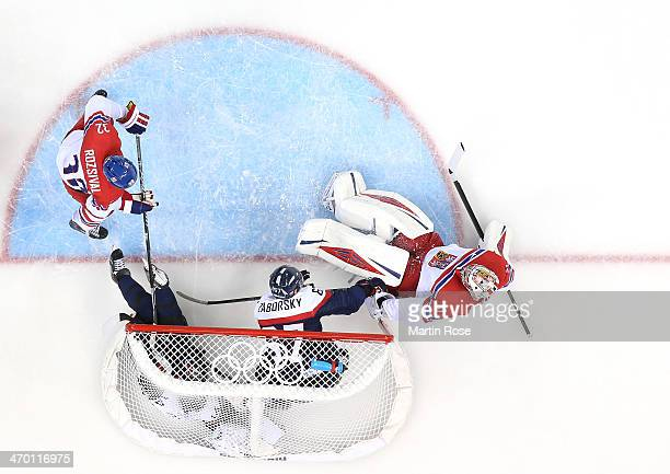 Andrej Meszaros and Tomas Zaborksy of Slovakia crash into the net of Ondrej Pavelec of Czech Republic in the first period during the Men's...