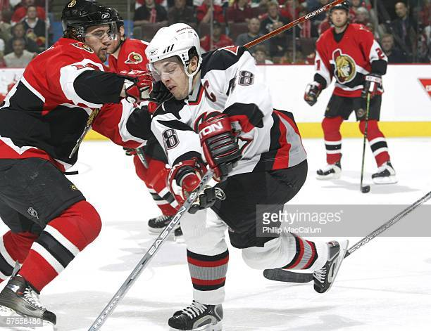 Andrej Meszaros of the Ottawa Senators checks Daniel Briere of the Buffalo Sabres during the first period of game two of the Eastern Conference...