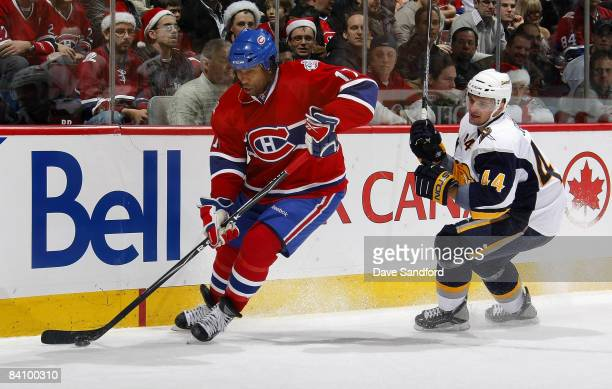 Andrej Sekera of the Buffalo Sabres defendsa against Georges Laraque of the Montreal Canadiens during their NHL game at the Bell Centre December 20...