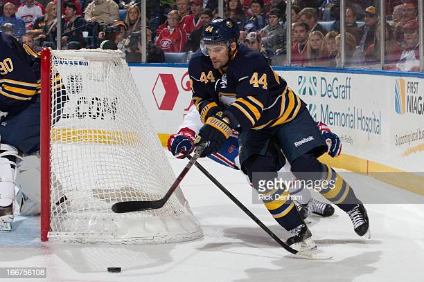 Andrej Sekera of the Buffalo Sabres tries to fight off a fore checking Montreal Canadiens player during the NHL game at First Niagara Center on April...