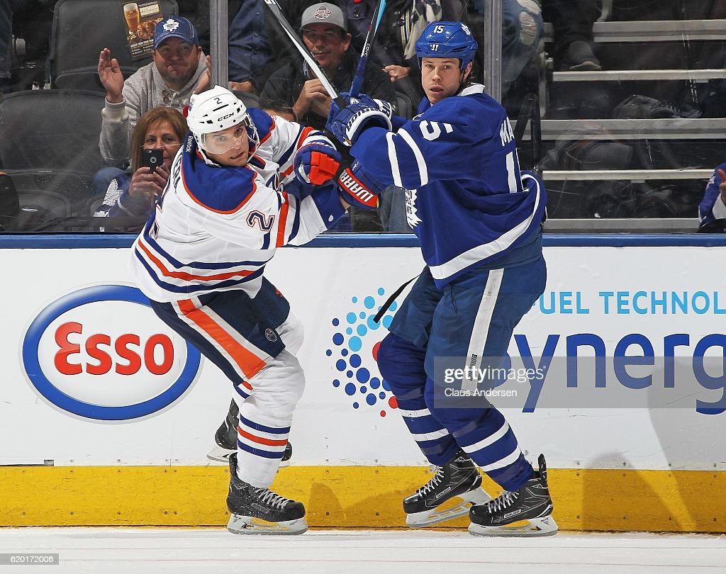 Andrej Sekera of the Edmonton Oilers battles against Matt Martin #15 of the Toronto Maple Leafs during an NHL game at the Air Canada Centre on November 1, 2016 in Toronto, Ontario, Canada. The Leafs defeated the Oilers 3-2 in overtime.