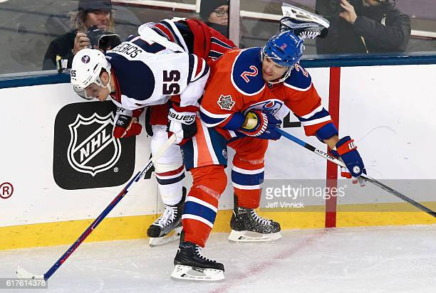 Andrej Sekera of the Edmonton Oilers checks Mark Scheifele of the Winnipeg Jets during the third period of the 2016 Tim Hortons NHL Heritage Classic...