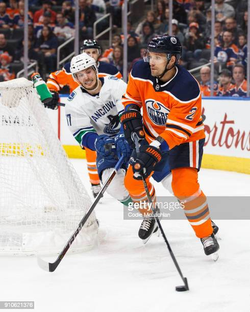 Andrej Sekera of the Edmonton Oilers is pursued by Nic Dowd of the Vancouver Canucks at Rogers Place on January 20 2018 in Edmonton Canada