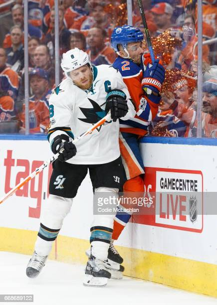 Andrej Sekera of the Edmonton Oilers is taken into the boards by Joe Pavelski of the San Jose Sharks in Game Two of the Western Conference First...