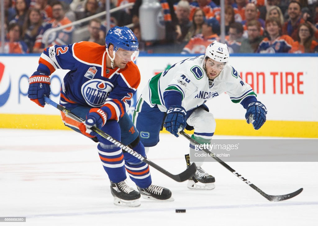 Andrej Sekera #2 of the Edmonton Oilers keeps the puck away from Michael Chaput #45 of the Vancouver Canucks on April 9, 2017 at Rogers Place in Edmonton, Alberta, Canada. The Oilers won 5-2.