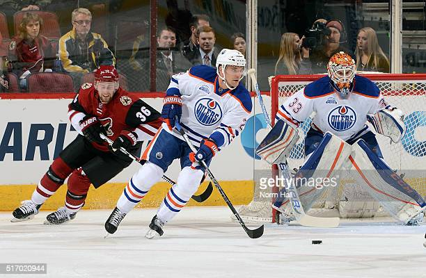 Andrej Sekera of the Edmonton Oilers skates with the puck in front of goaltender Cam Talbot of the Oilers as Jiri Sekac of the Arizona Coyotes trails...