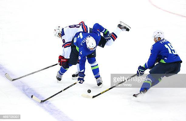 Andrej Tavzelj and Ziga Pance of Slovenia try to handle the puck against Joe Pavelski of the United States in the third period during the Men's Ice...