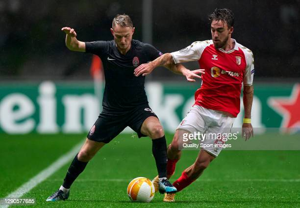 Andrejs Ciganiks of Zorya Luhansk competes for the ball with Andre Horta of SC Braga during the UEFA Europa League Group G stage match between SC...