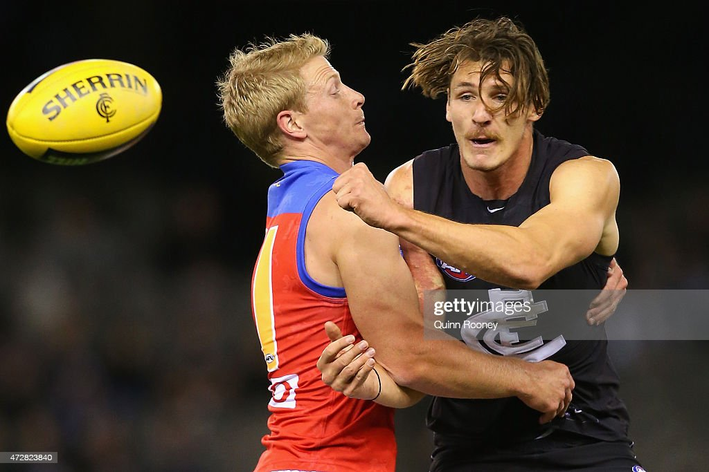 Andrejs Everitt of the Blues handballs whilst being tackled by Mitch Golby of the Lions during the round six AFL match between the Carlton Blues and the Brisbane Lions at Etihad Stadium on May 10, 2015 in Melbourne, Australia.