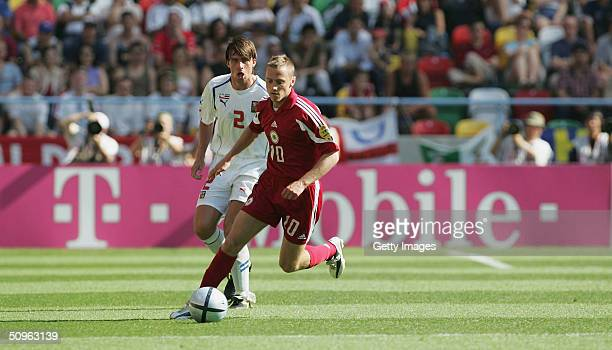 Andrejs Rubins of Latvia battles with Zdenek Grygera of the Czech Republic during the UEFA Euro 2004 Group D match between Czech Republic and Latvia...