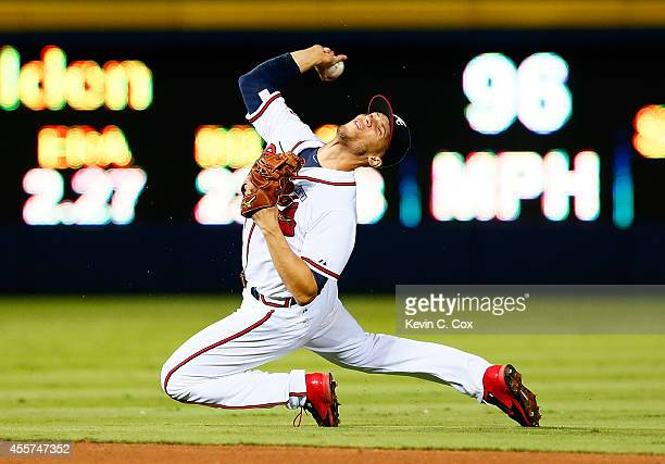 Andrelton Simmons of the Atlanta Braves attempts to make a play on a single hit by Wilmer Flores of the New York Mets in the ninth inning at Turner...