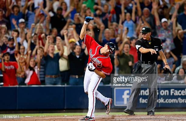 Andrelton Simmons of the Atlanta Braves scores the gamewinning run on a walkoff single by Tyler Pastornicky in the ninth inning against the...