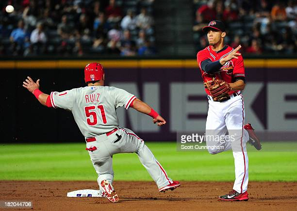 Andrelton Simmons of the Atlanta Braves turns a double play against Carlos Ruiz of the Philadelphia Phillies at Turner Field on September 27 2013 in...