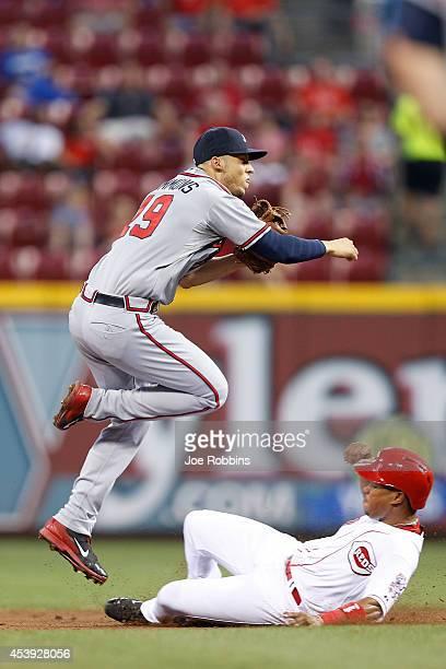 Andrelton Simmons of the Atlanta Braves turns a double play against Ramon Santiago of the Cincinnati Reds in the third inning of the game at Great...