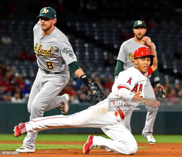 Andrelton Simmons of the Los Angeles Angels is tagged out by Jed Lowrie of the Oakland Athletics as he is caught in a run down in the fifth inning of...