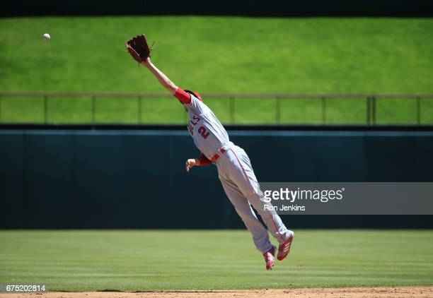 Andrelton Simmons of the Los Angeles Angels of Anaheim leaps for a run scoring single by Carlos Gomez of the Texas Rangers in the first inning at...