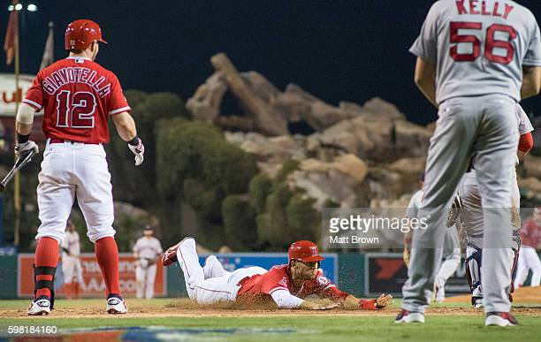 Andrelton Simmons of the Los Angeles Angels of Anaheim makes a diving slide to score on a RBI double by Jett Bandy during the sixth inning of the...