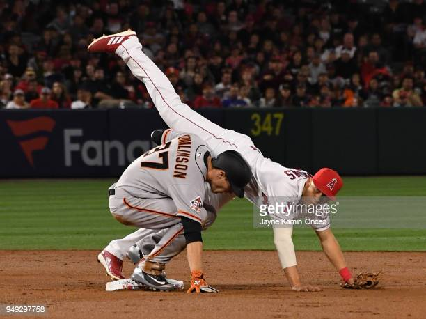 Andrelton Simmons of the Los Angeles Angels of Anaheim us upended by Kelby Tomlinson of the San Francisco Giants at he completes a double play in the...