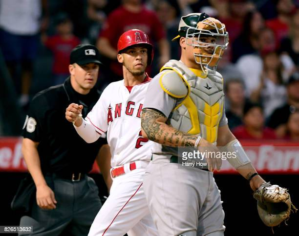 Andrelton Simmons of the Los Angeles Angels scores behind Bruce Maxwell of the Oakland Athletics on a fielding error during the second inning at...