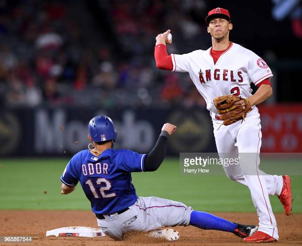 Andrelton Simmons of the Los Angeles Angels turns a double play as Rougned Odor of the Texas Rangers slides at second base to end the game during the...