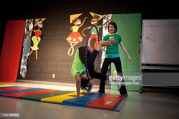 Andrenae Brown does a tumbling act as Christine Soykal holds the hula hoop at the performance capping an after school circus class taught by members...