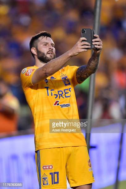 AndrePierre Gignac #10 of Tigres celebrates by taking a selfie after scoring his team's second goal during the 13th round match between Tigres UANL...