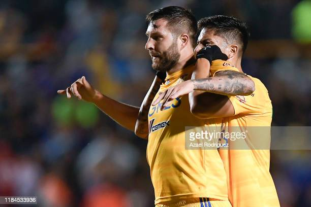 AndrePierre Gignac #10 of Tigres celebrates with teammate Carlos Salcedo #3 after scoring his team's first goal during the 16th round match between...
