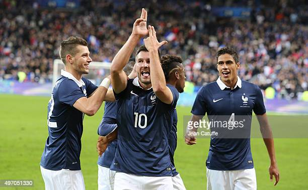 Andre-Pierre Gignac of France celebrates scoring a goal with Laurent Koscielny and Raphael Varane of France during the international friendly match...