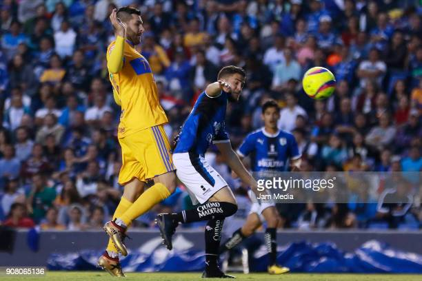 AndrePierre Gignac of Tigres and Hiram Mier of Queretaro fight for the ball during the third round match between Queretaro and Tigres UANL as part of...