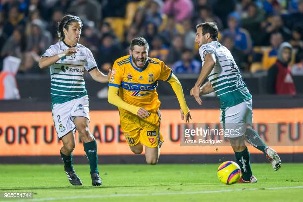 AndrePierre Gignac of Tigres falls to the ground while he fights for the ball with Jose Abella and Carlos Izquierdoz of Santos during the 2nd round...