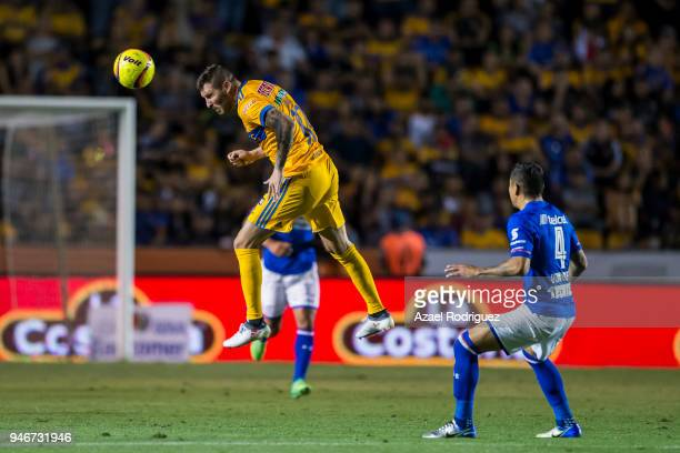 AndrePierre Gignac of Tigres heads the ball while observed by Julio Dominguez of Cruz Azul during the 15th round match between Tigres UANL and Cruz...