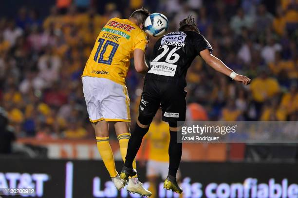 AndrePierre Gignac of Tigres heads the ball with Cristian Calderón of Necaxa and scores his team's second goal during the seventh round match between...