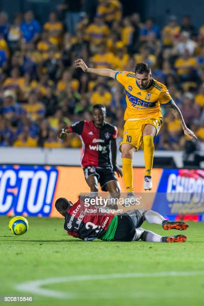 AndrePierre Gignac of Tigres jumps over Leyton Jimenez of Atlas during the 8th round match between Tigres UANL and Atlas as part of the Torneo...