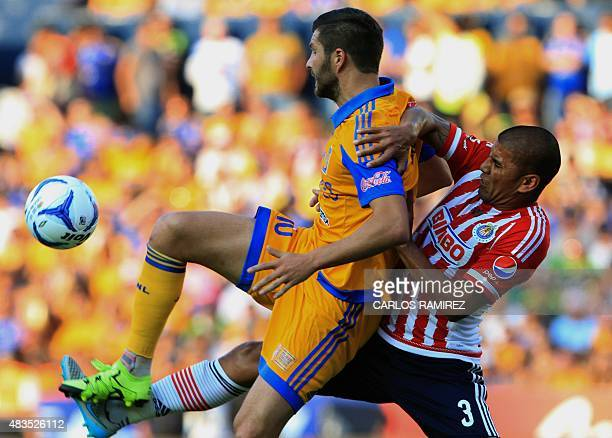 AndrePierre Gignac of Tigres vies for the ball with Carlos Salcido of Chivas during their Mexican Apertura football tournament in Monterrey Nuevo...