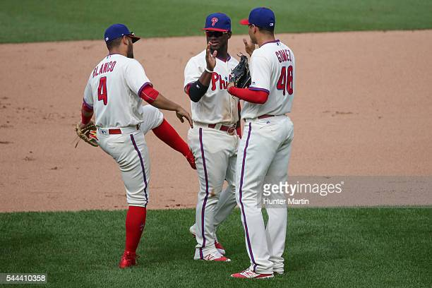 Andres Blanco of the Philadelphia Phillies gives a playful kick in the butt to Odubel Herrera after winning a game against the Kansas City Royals at...