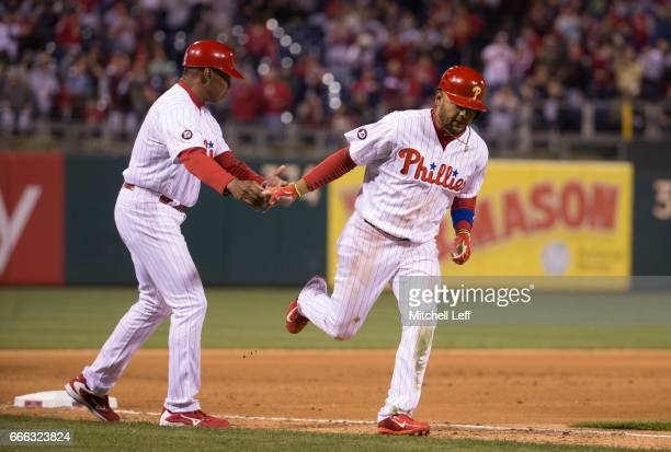 Andres Blanco of the Philadelphia Phillies rounds third base after his solo home run and is congratulated by third base coach Juan Samuel of the...