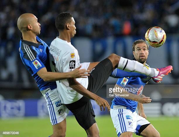 Andres Cadavid and Federico Insua of Millonarios struggle for the ball with Deivy Balanta of Alianza Petrolera during a match between Millonarios and...