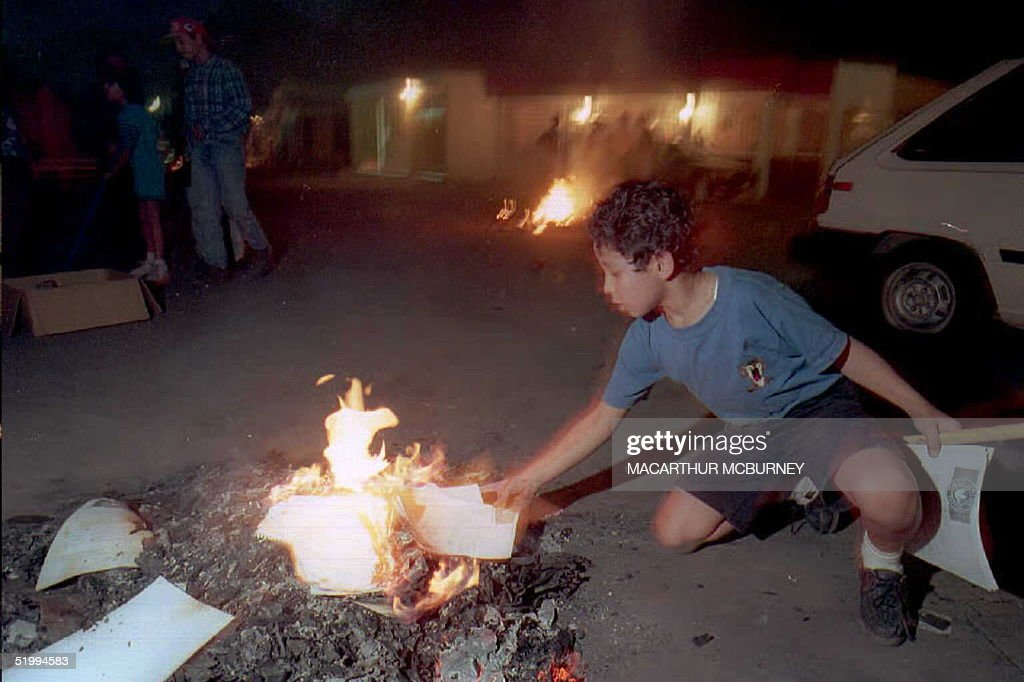 Andres Castellanos Eight Throws Old School Papers On A Fire Outside His Home In