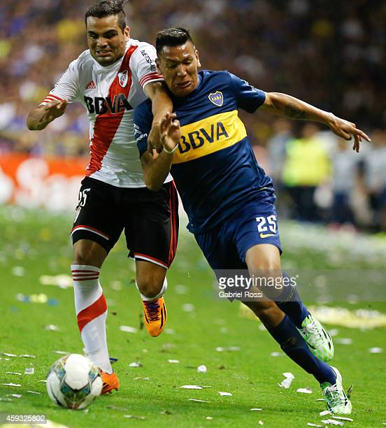 Andres Chavez of Boca Juniors fights for the ball with Gabriel Mercado of River Plate during a first leg semifinal match between Boca Juniors and...