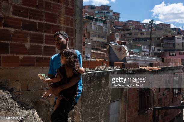 Andres Colima carries his stepchild up the stairs to the family's home in La Agricultura an impoverished neighborhood in Caracas Venezuela on...