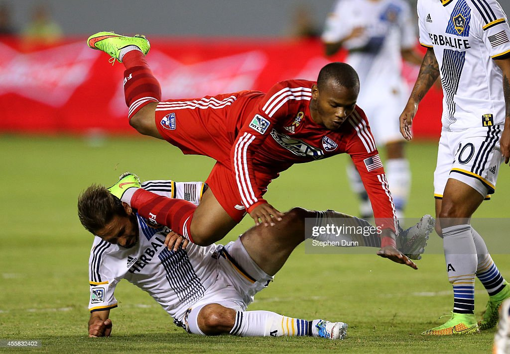 Andres Escobar #91 of FC Dallas falls over Marcelo Sarvas #8 of of the Los Angeles Galaxy at StubHub Center on September 20, 2014 in Los Angeles, California.