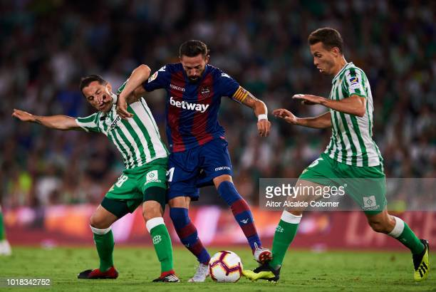 Andres Guardado and Sergio Canales of Real Betis compete for the ball with Jose Luis Morales of Levante UD during the La Liga match between Real...