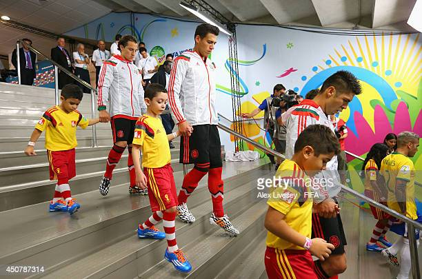 Andres Guardado Hector Moreno and Oribe Peralta of Mexico walk with their player escorts to take the field prior to the 2014 FIFA World Cup Brazil...