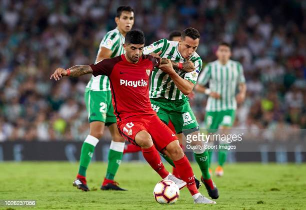 Andres Guardado of Betis competes for the ball with Ever Banega of Sevila during the La Liga match between Real Betis Balompie and Sevilla FC at...